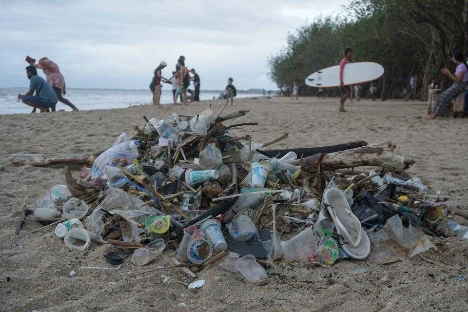 Tourists are seen walking along the beach with garbage in the ...